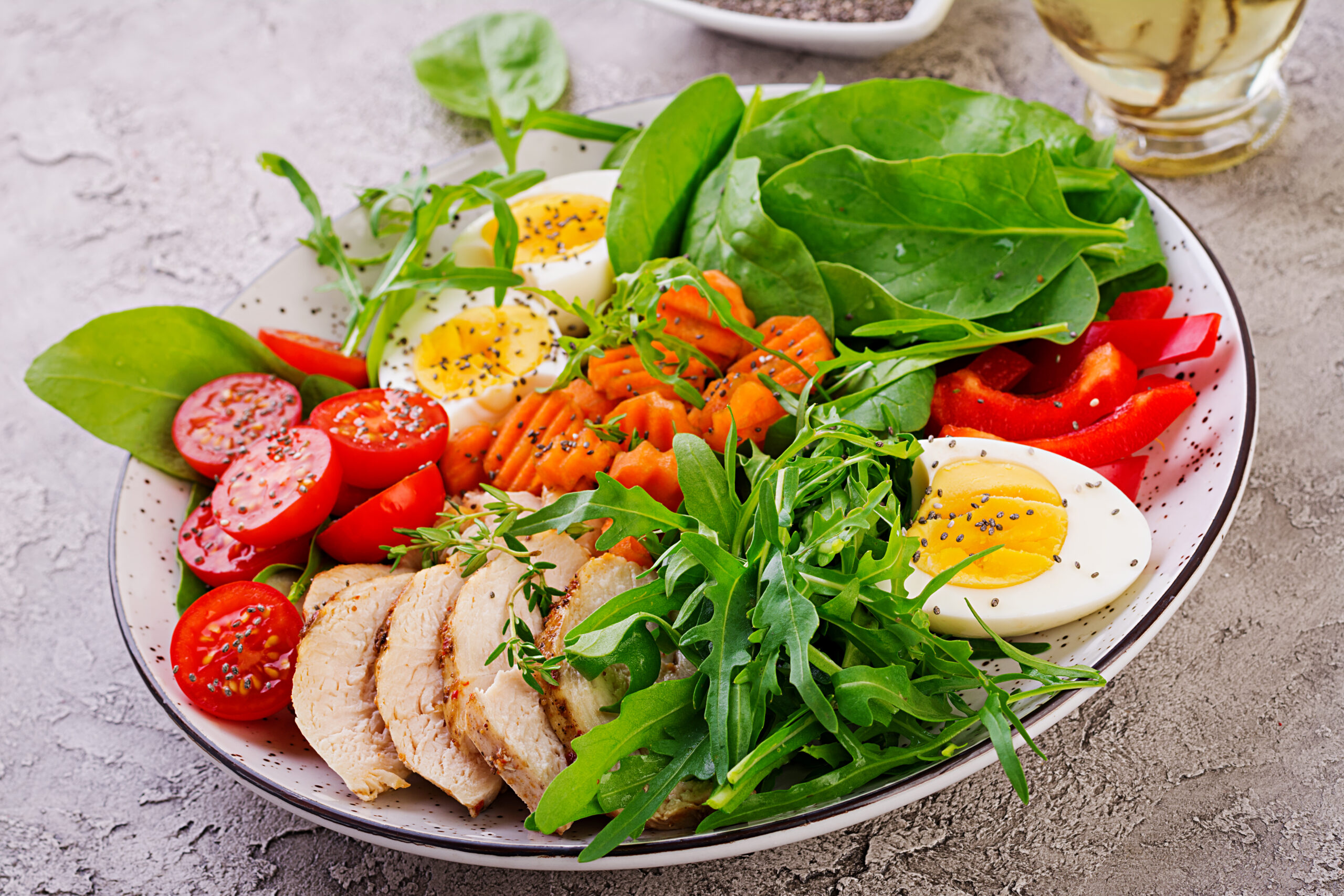 Plate with a keto diet food. Cherry tomatoes, chicken breast, eggs, carrot, salad with arugula  and spinach. Keto lunch